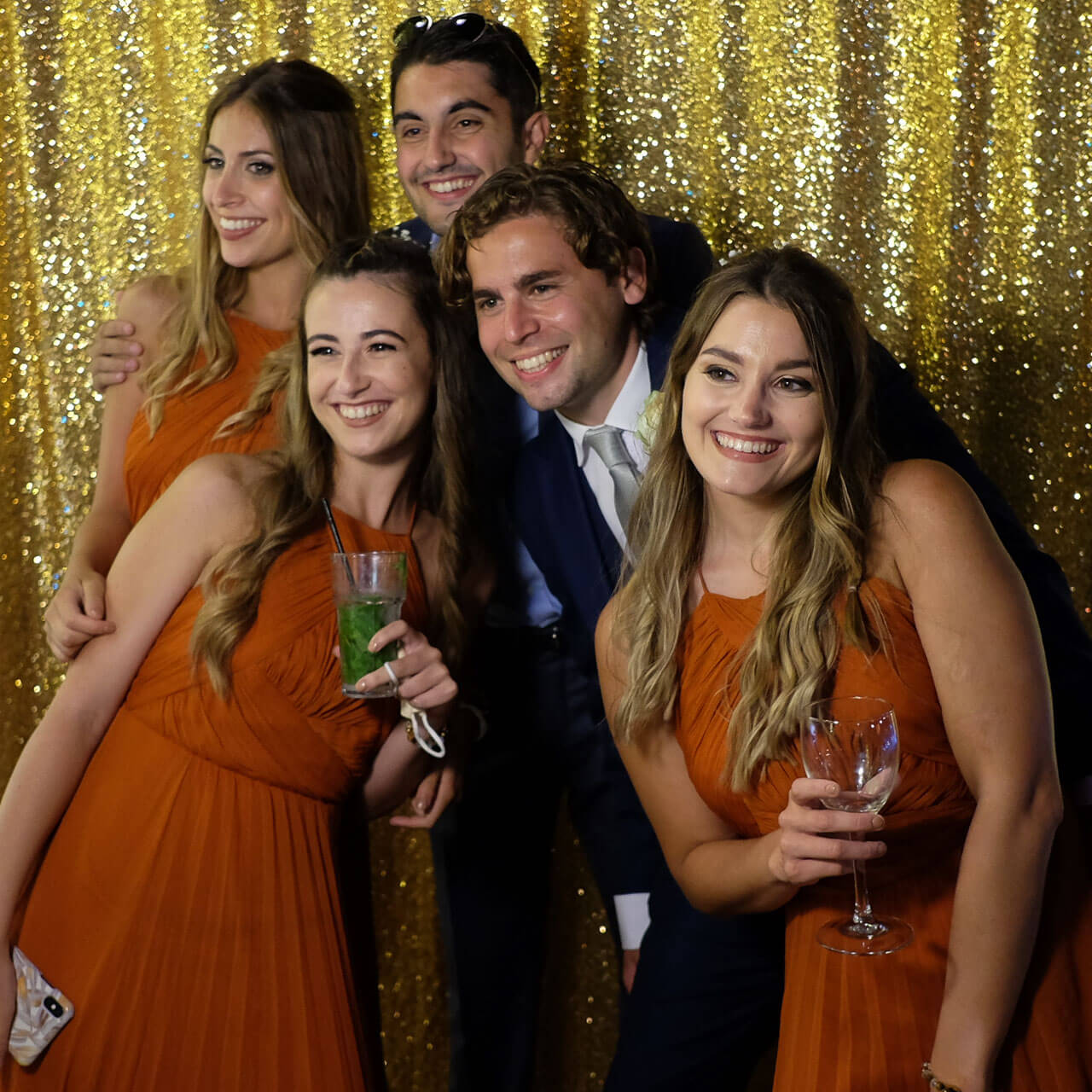 A lovely group of people posing in fornt of a gold glitter backdrop